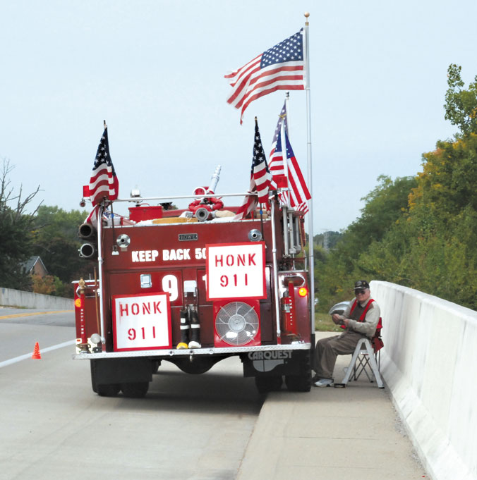 photo by C.J. Woods IIIVeteran Bill Watson sets up his firetruck and flags at the 16th St. overpass every September 11 to honor the fallen. His patriotic display gets lots of thumbs-up and honks from motorists every year.